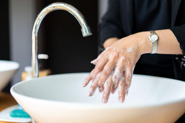 Femme en costume noir foncé se lave la main dans l'évier.
