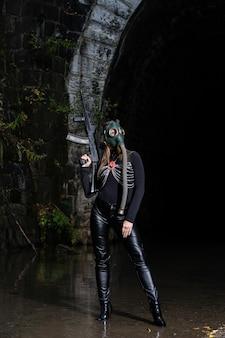 Une femme en costume noir et masque à gaz avec une mitrailleuse dans les mains