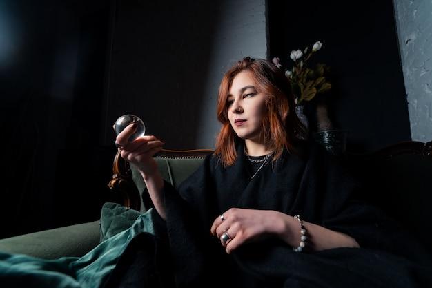Femme en costume noir tenant une boule de cristal dans ses mains