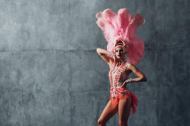 Femme en costume de samba ou de lambada au plumage de plumes roses.
