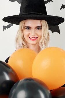 Femme en costume de sorcière posant avec des ballons