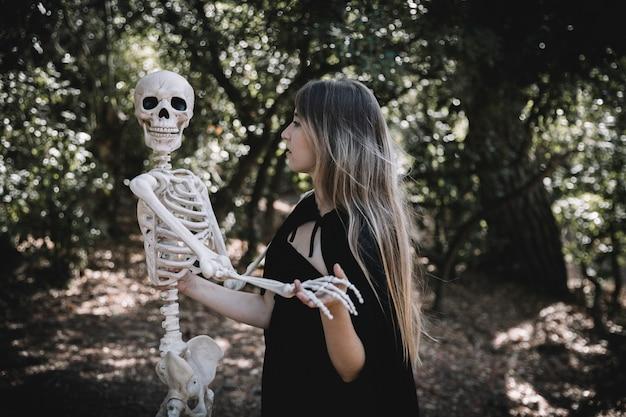 Femme en costume de sorcière tenant un squelette