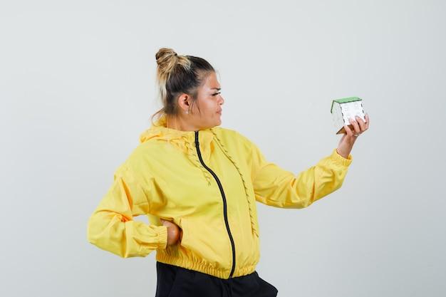 Femme en costume de sport à la recherche de modèle de maison et à la vue de face focalisée.