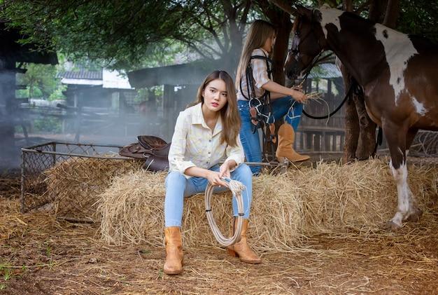 Femme en costume de style cow-girl dans un ranch de chevaux avec un environnement agricole occidental.
