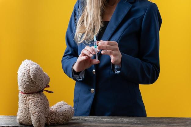 Femme en costume tenant une seringue médicale avec ours en peluche sur un bureau