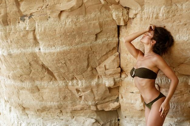 Femme à côté d'une falaise de sable