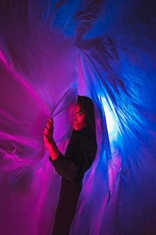 Femme de côté avec une feuille de plastique