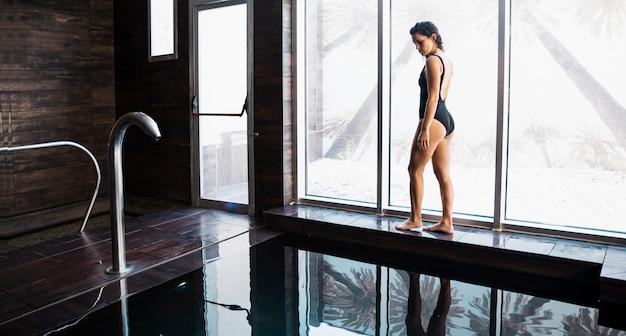 Femme à côté de la piscine au spa