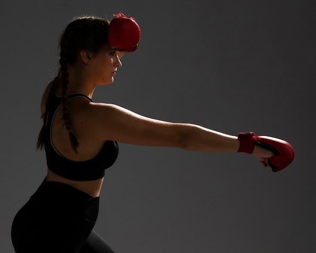 Femme de côté poinçonnant avec des gants