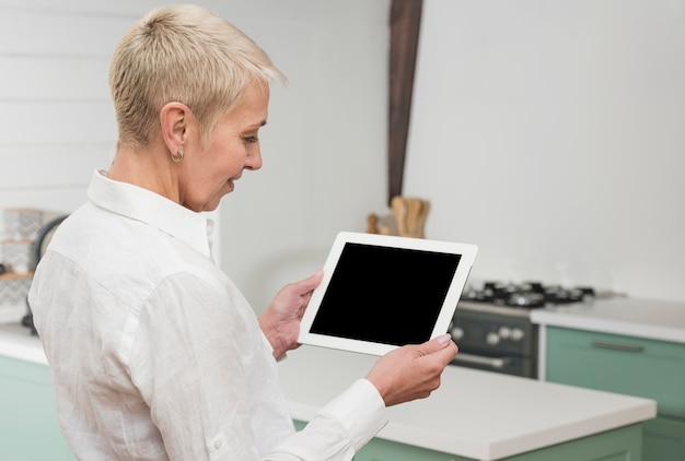 Femme de côté à la recherche sur sa tablette