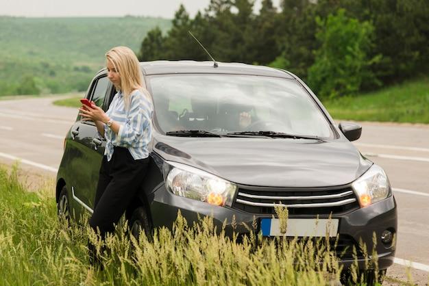 Femme à côté de sa voiture en panne