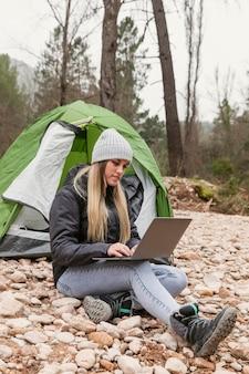Femme à côté de la tente avec ordinateur portable
