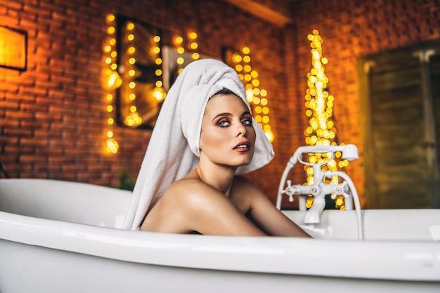 Femme couchée dans un bain blanc avec une serviette sur la tête