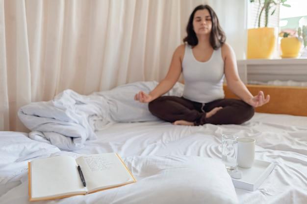 Femme couchée dans son lit méditant à côté de journal ou de cahier