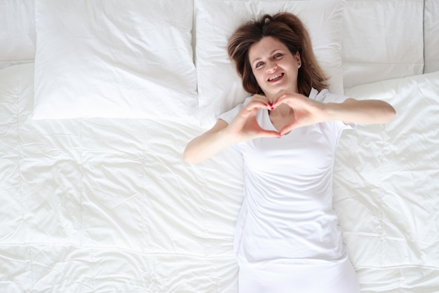 Femme couchée dans son lit et montrant le coeur avec sa vue de dessus de mains. l'amour dans le concept de distance