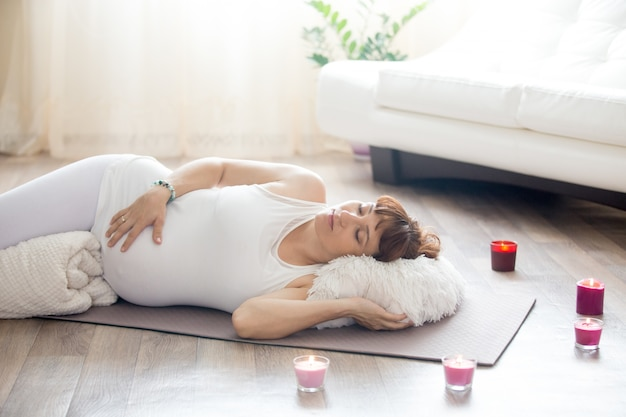 Femme couchée sur le sol avec des bougies autour