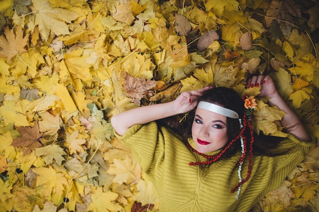 Femme couchée sur le sol avec des feuilles sèches