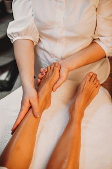 Femme couchée tout en ayant une procédure de spa pour la peau de ses jambes au salon