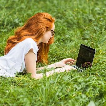 Femme, coucher herbe, à, ordinateur portable