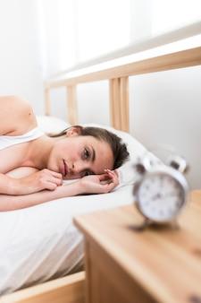 Femme, coucher lit, à, réveil, sur, bureau bois