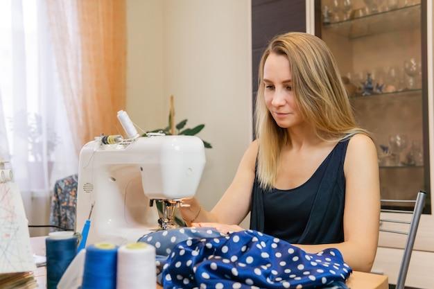 Une femme coud du tissu bleu sur une machine à coudre à la maison