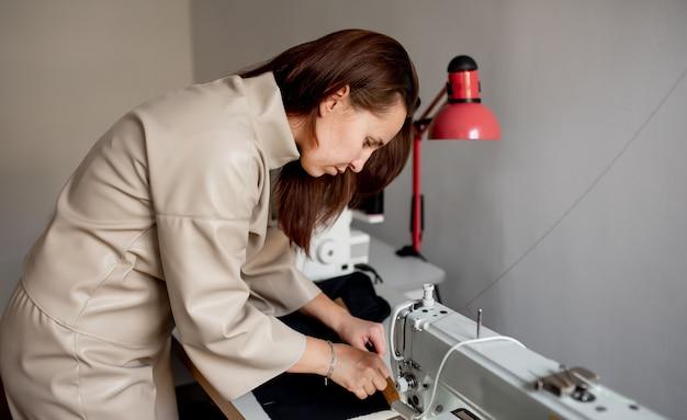 Une femme coud un tissu sombre sur une machine à coudre.