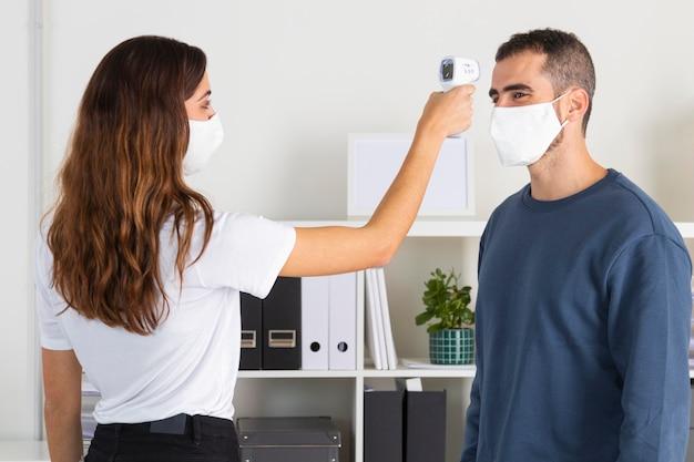 Femme coup moyen avec appareil de température