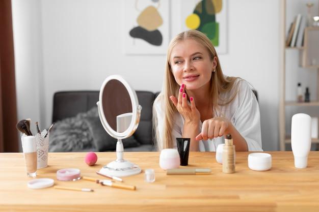 Femme de coup moyen appliquant la crème pour le visage