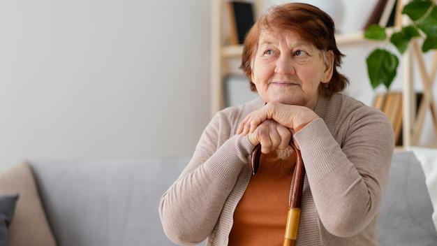 Femme coup moyen avec bâton de marche
