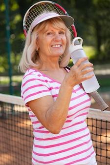 Femme de coup moyen avec une bouteille d'eau