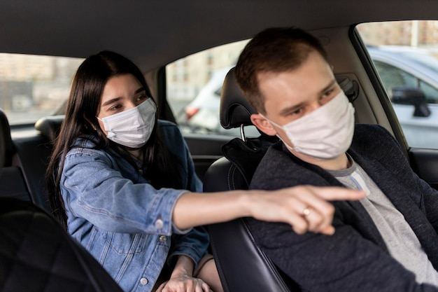Femme de coup moyen et chauffeur avec masque