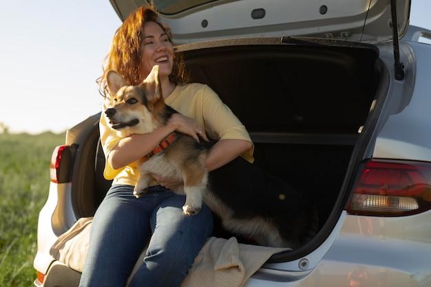 Femme de coup moyen avec un chien et une voiture mignons