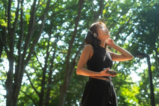 Femme de coup moyen avec des écouteurs dans la nature