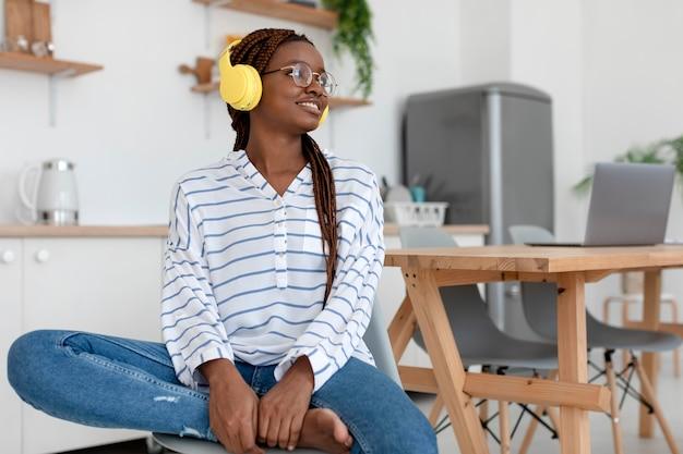 Femme de coup moyen avec des écouteurs jaunes