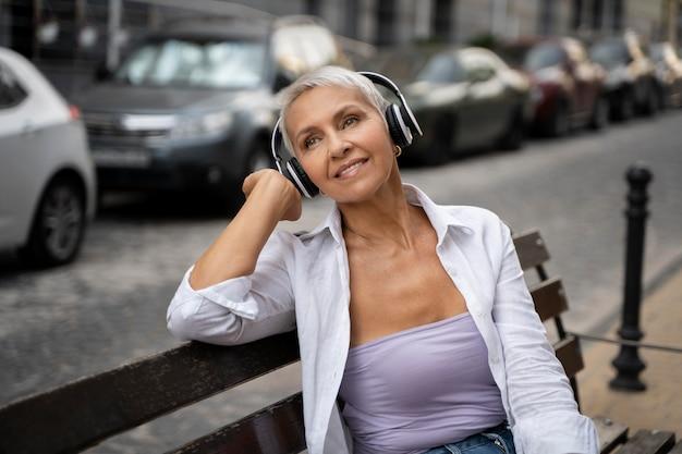 Femme de coup moyen avec des écouteurs