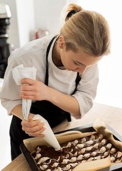 Femme coup moyen faisant le dessert