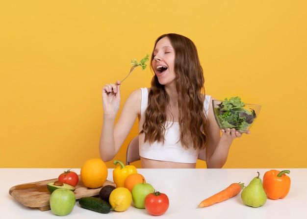 Femme de coup moyen avec des légumes sains