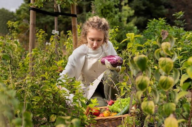 Femme de coup moyen avec des légumes