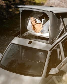 Femme coup moyen avec livre pendant le road trip