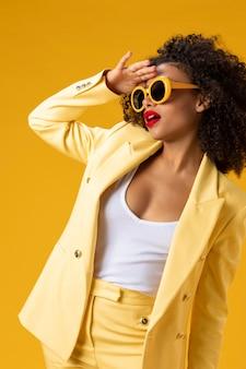 Femme de coup moyen avec des lunettes de soleil jaunes