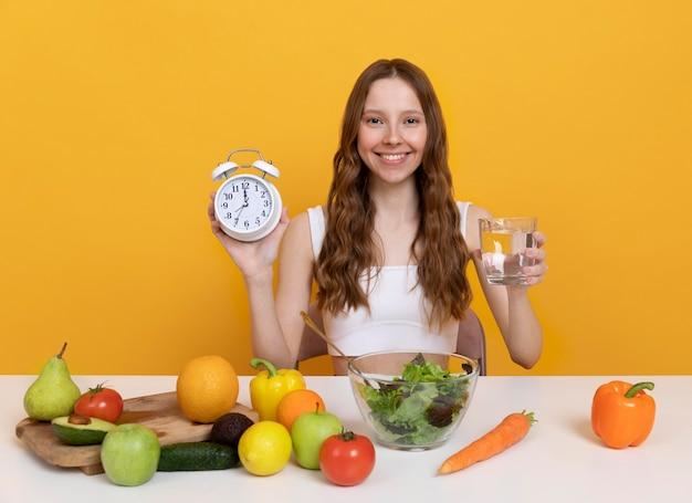 Femme de coup moyen avec de la nourriture et une horloge