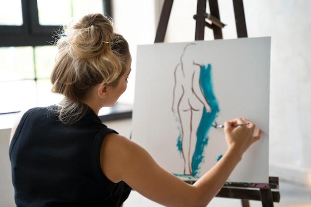Femme de coup moyen peignant sur toile