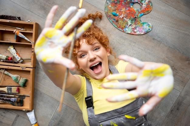 Femme de coup moyen avec de la peinture sur les mains
