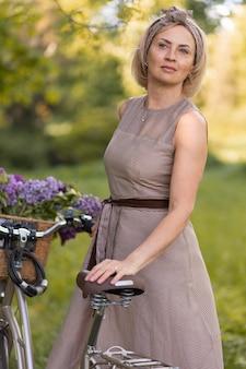 Femme de coup moyen près de vélo