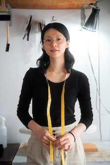 Femme de coup moyen avec un ruban à mesurer