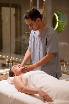 Femme de coup moyen se faisant masser