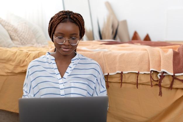 Femme de coup moyen se relaxant avec un ordinateur portable