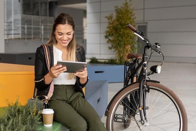 Femme coup moyen avec tablette et vélo