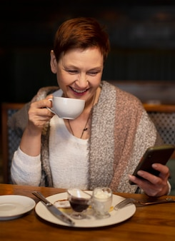 Femme coup moyen avec tasse et téléphone