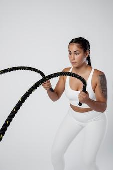 Femme de coup moyen travaillant avec une corde